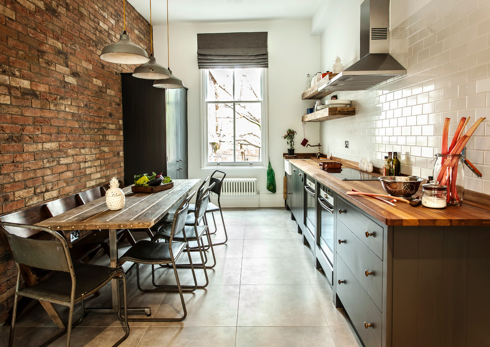 Mid-sized urban single-wall enclosed kitchen photo in London with wood countertops, white backsplash, subway tile backsplash and no island