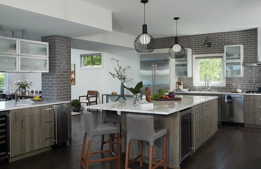 Klassische Küche mit flächenbündigen Schrankfronten, Küchenrückwand in Grau, Rückwand aus Metrofliesen, Küchengeräten aus Edelstahl, dunklem Holzboden, Kücheninsel und braunem Boden in Grand Rapids