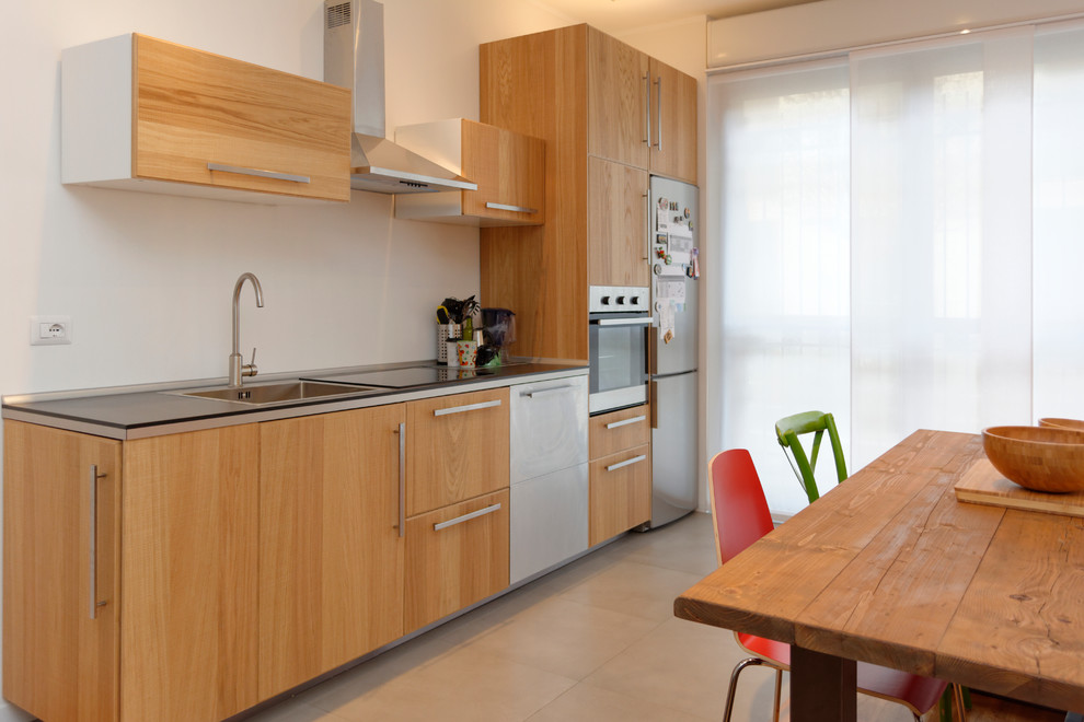 Example of a mid-sized trendy single-wall concrete floor eat-in kitchen design in Milan with a single-bowl sink, flat-panel cabinets, medium tone wood cabinets, laminate countertops, white backsplash and stainless steel appliances