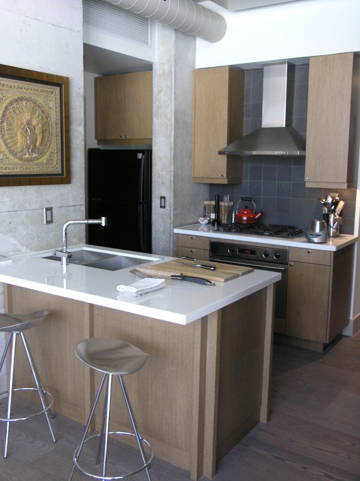 Example of a trendy kitchen design in Toronto with flat-panel cabinets, light wood cabinets, gray backsplash and stainless steel appliances