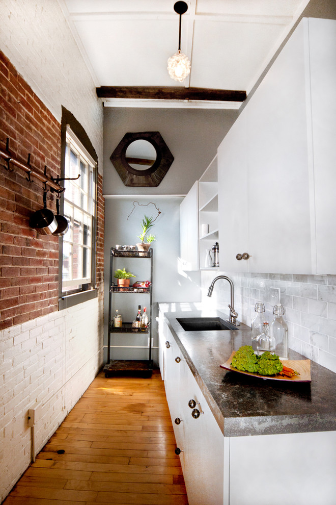 Inspiration for an industrial enclosed kitchen remodel in Portland Maine with an undermount sink, flat-panel cabinets, white cabinets, white backsplash and subway tile backsplash