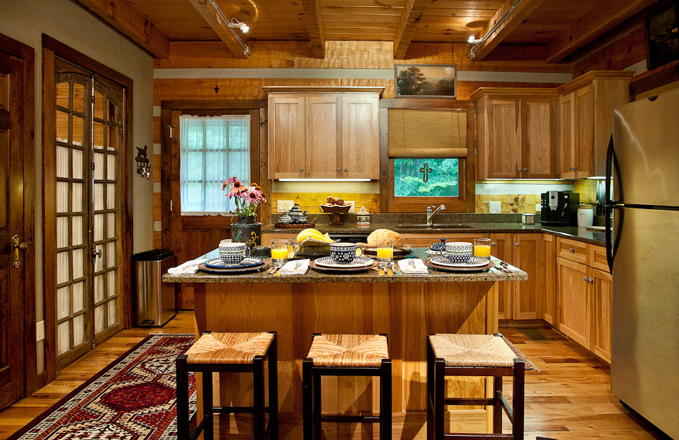 Open concept kitchen - mid-sized rustic l-shaped medium tone wood floor open concept kitchen idea in Nashville with stainless steel appliances, an undermount sink, shaker cabinets, medium tone wood cabinets, granite countertops and brown backsplash