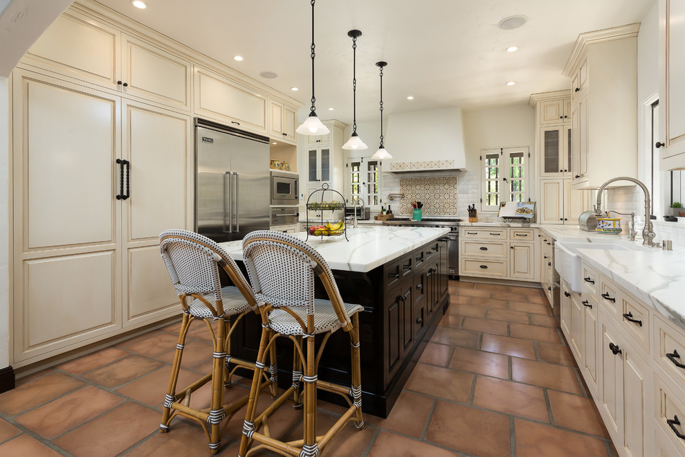 Inspiration for a mediterranean u-shaped terra-cotta tile kitchen remodel in Los Angeles with a farmhouse sink, raised-panel cabinets, beige cabinets, multicolored backsplash, stainless steel appliances, an island and marble countertops