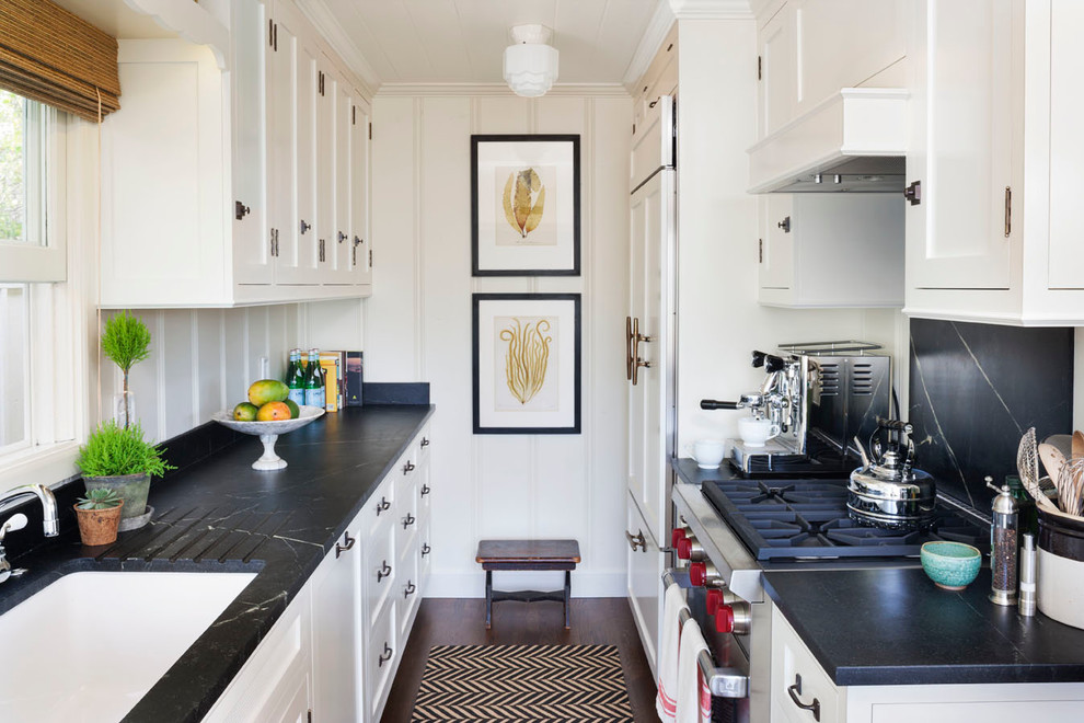 Example of a small beach style galley dark wood floor kitchen design in Orange County with a single-bowl sink, shaker cabinets, white cabinets, black backsplash and no island