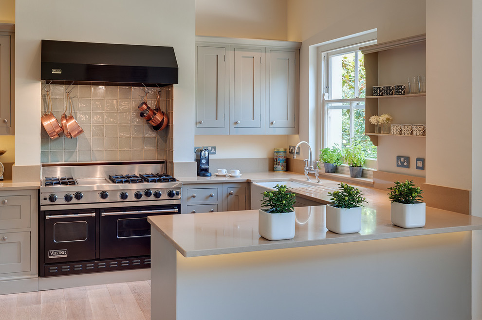 Example of a classic u-shaped light wood floor kitchen design in London with a farmhouse sink, shaker cabinets, gray cabinets, black appliances, a peninsula and gray backsplash