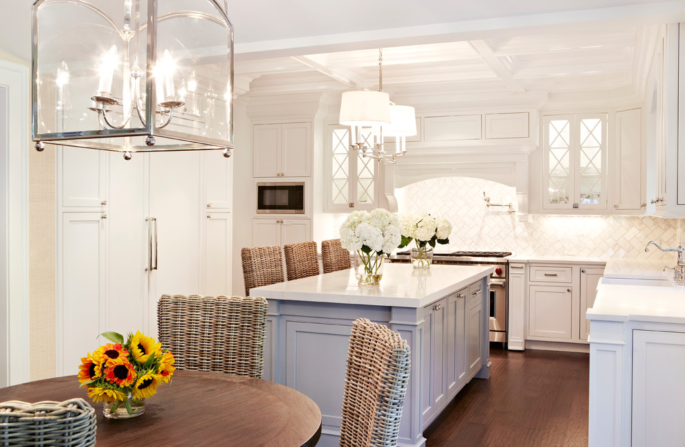 Inspiration for a coastal u-shaped dark wood floor eat-in kitchen remodel in New York with a farmhouse sink, shaker cabinets, white cabinets, white backsplash, stainless steel appliances and an island