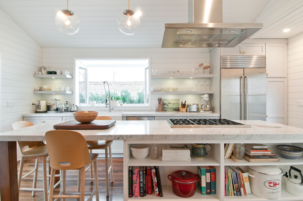 Eat-in kitchen - mid-sized country galley painted wood floor eat-in kitchen idea in Los Angeles with a farmhouse sink, shaker cabinets, white cabinets, white backsplash, an island, marble countertops, wood backsplash and stainless steel appliances
