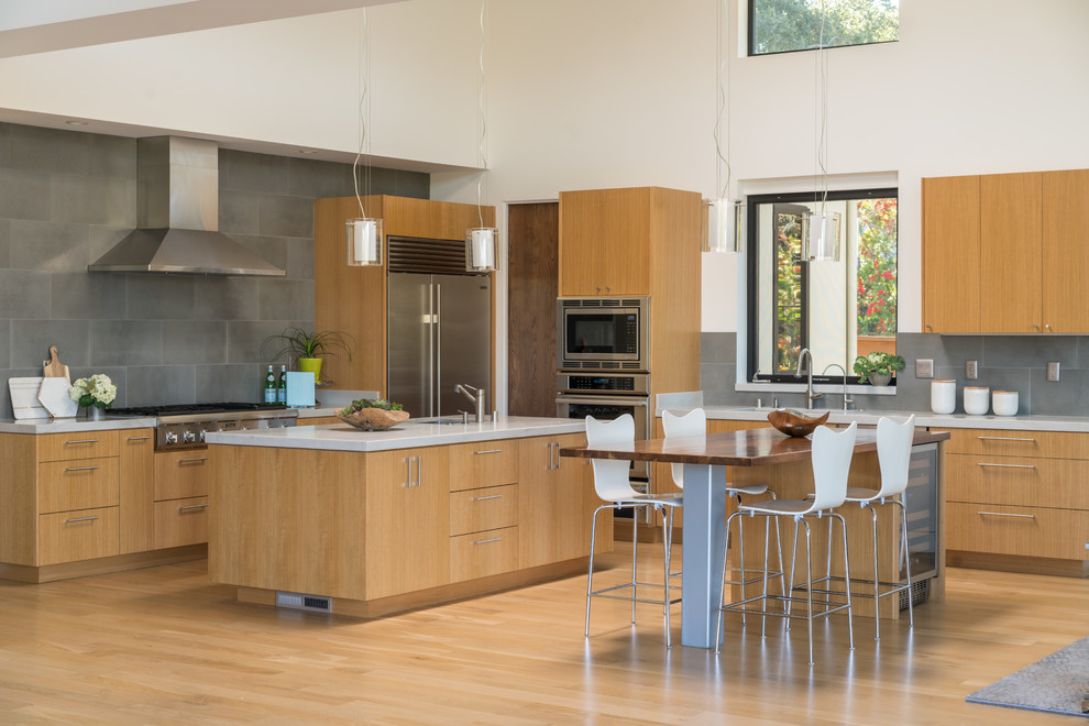 Example of a trendy l-shaped light wood floor and brown floor eat-in kitchen design in San Francisco with an undermount sink, flat-panel cabinets, medium tone wood cabinets, gray backsplash, stainless steel appliances and two islands