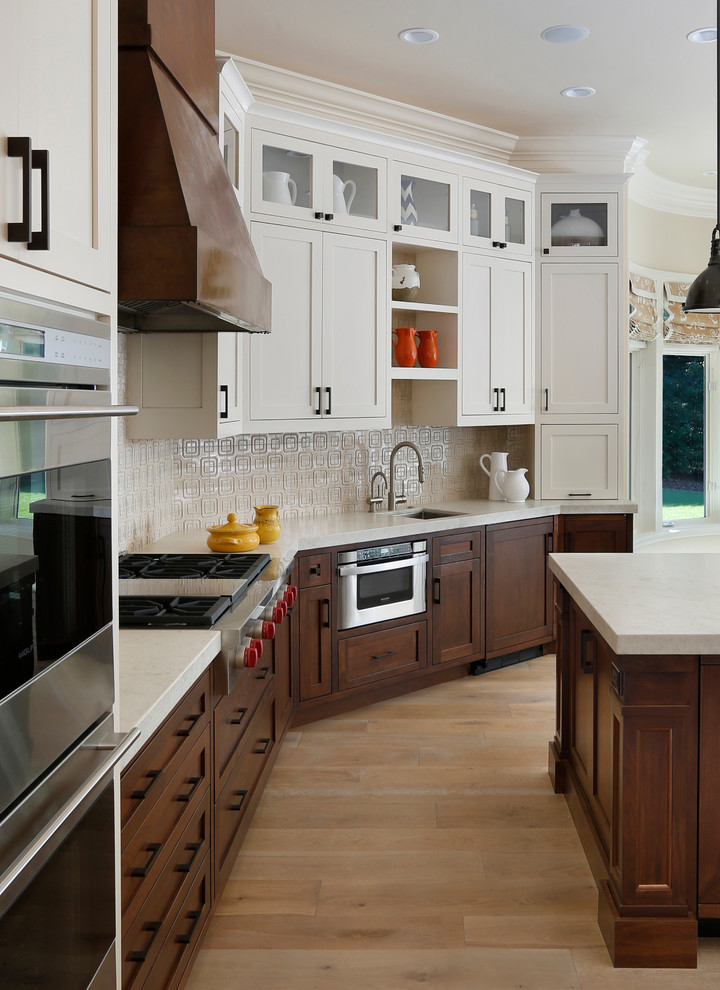 Kitchen - transitional kitchen idea in San Francisco with an undermount sink, dark wood cabinets, recessed-panel cabinets, white backsplash and stainless steel appliances