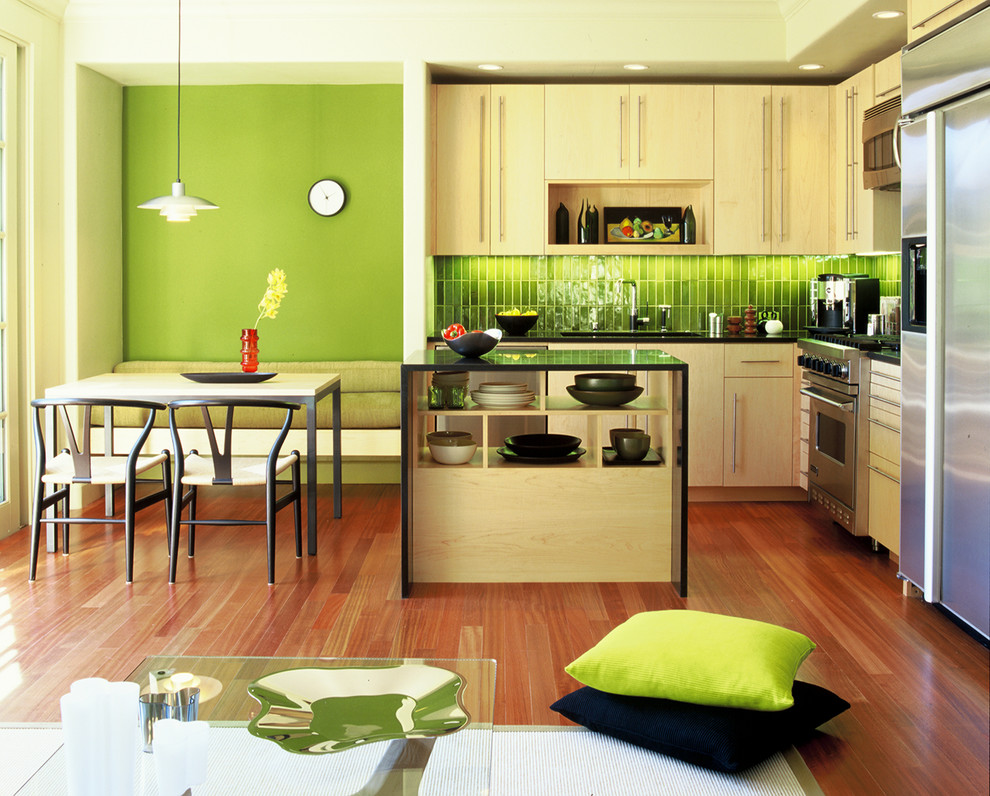 Eat-in kitchen - modern l-shaped eat-in kitchen idea in San Francisco with stainless steel appliances, an undermount sink, flat-panel cabinets, light wood cabinets and green backsplash