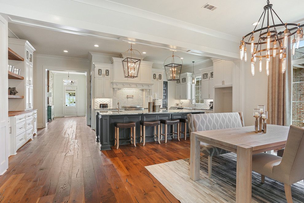 Example of a large cottage single-wall dark wood floor and brown floor eat-in kitchen design in New Orleans with an undermount sink, recessed-panel cabinets, white cabinets, granite countertops, white backsplash, ceramic backsplash, stainless steel appliances, an island and gray countertops