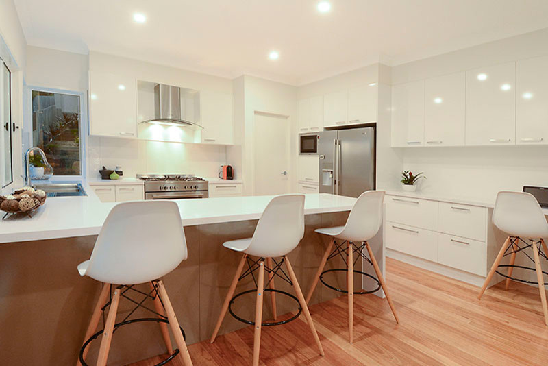 Inspiration for a mid-sized contemporary u-shaped light wood floor open concept kitchen remodel in Brisbane with a double-bowl sink, flat-panel cabinets, white cabinets, white backsplash, glass sheet backsplash, stainless steel appliances, a peninsula, wood countertops and white countertops