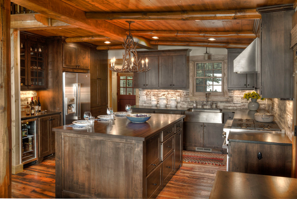 Mountain style u-shaped dark wood floor kitchen photo in Minneapolis with a farmhouse sink, shaker cabinets, dark wood cabinets, stainless steel appliances and an island