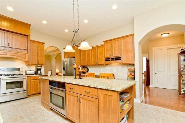 Eat-in kitchen - large traditional u-shaped light wood floor eat-in kitchen idea in Columbus with a double-bowl sink, recessed-panel cabinets, light wood cabinets, granite countertops, beige backsplash, ceramic backsplash, stainless steel appliances and an island