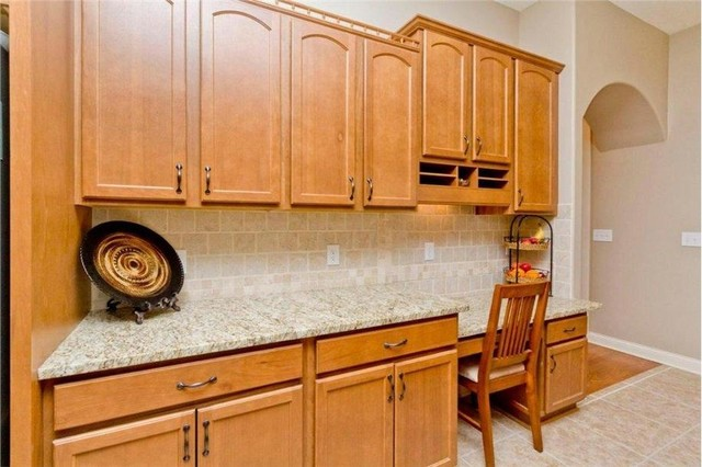 Example of a large classic u-shaped light wood floor eat-in kitchen design in Columbus with a double-bowl sink, recessed-panel cabinets, light wood cabinets, granite countertops, beige backsplash, ceramic backsplash, stainless steel appliances and an island