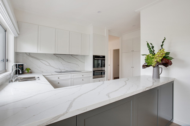 This is an example of a large contemporary u-shaped open plan kitchen in Sydney with a drop-in sink, shaker cabinets, white cabinets, quartz benchtops, white splashback, stone slab splashback, white appliances, medium hardwood floors, no island, beige floor and multi-coloured benchtop.