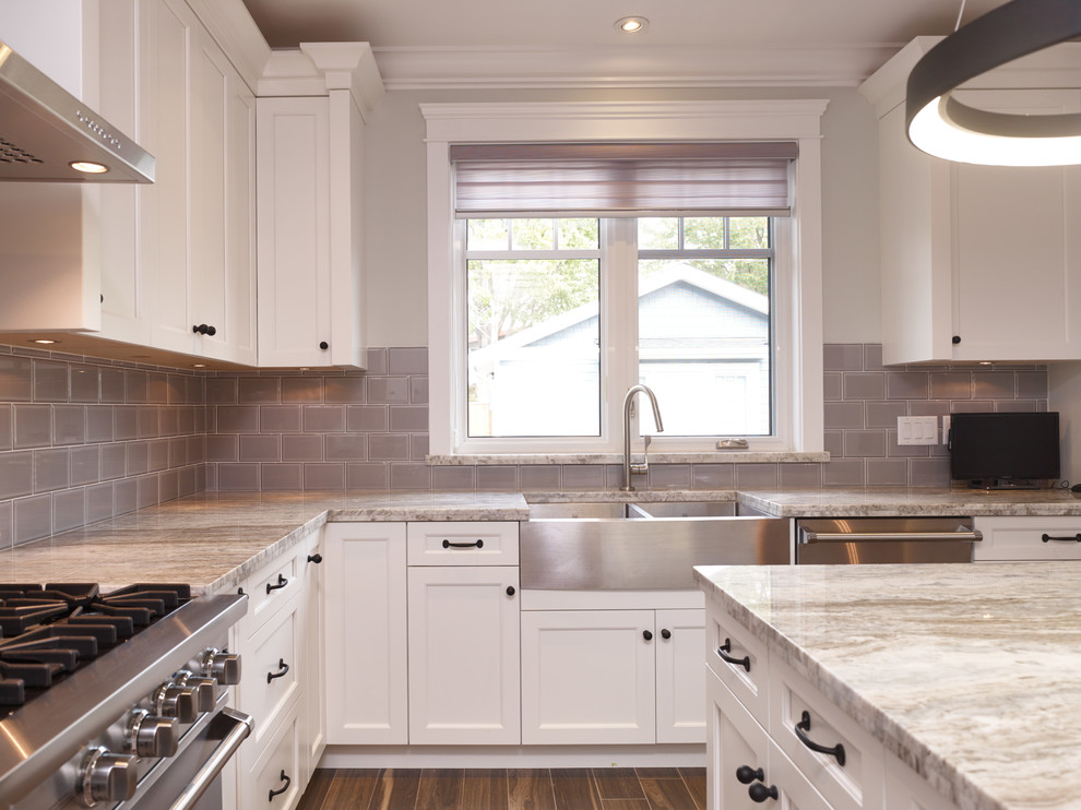 Kitchen - transitional u-shaped ceramic tile kitchen idea in Vancouver with an undermount sink, shaker cabinets, white cabinets, granite countertops, gray backsplash, subway tile backsplash, stainless steel appliances and an island