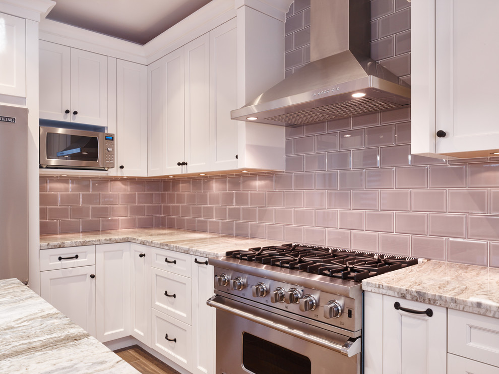 Example of a transitional u-shaped ceramic tile kitchen design in Vancouver with an undermount sink, shaker cabinets, white cabinets, granite countertops, gray backsplash, subway tile backsplash, stainless steel appliances and an island