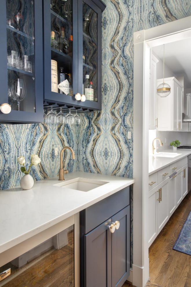 Small minimalist galley medium tone wood floor and brown floor kitchen pantry photo in DC Metro with an undermount sink, recessed-panel cabinets, blue cabinets, quartz countertops, blue backsplash, stainless steel appliances, no island and white countertops