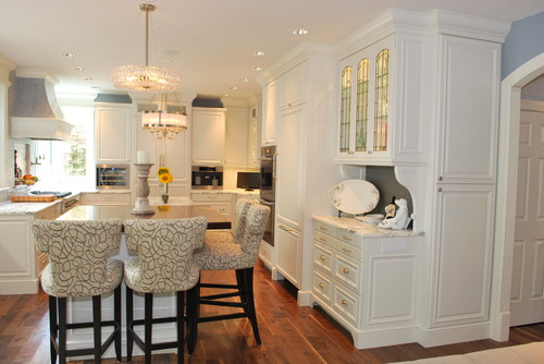 Traditional modern kitchen with white cabinets and hardwood flooring featuring four stools with patterned cushions