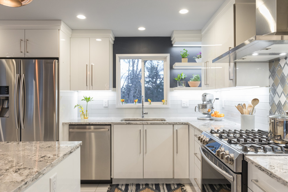 Inspiration for a mid-sized scandinavian l-shaped plywood floor eat-in kitchen remodel in Manchester with an undermount sink, flat-panel cabinets, white cabinets, quartz countertops, multicolored backsplash, glass sheet backsplash, stainless steel appliances and an island