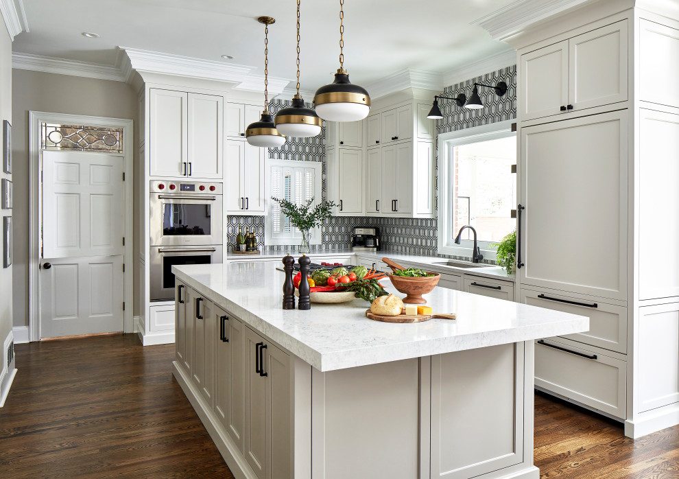 Example of a transitional l-shaped medium tone wood floor and brown floor eat-in kitchen design in Atlanta with an undermount sink, recessed-panel cabinets, white cabinets, multicolored backsplash, paneled appliances, an island and white countertops