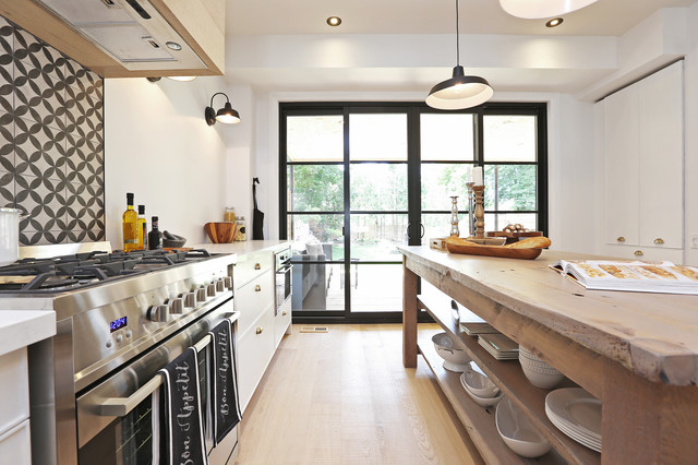 Large danish light wood floor open concept kitchen photo in Toronto with a farmhouse sink, flat-panel cabinets, white cabinets, quartzite countertops, multicolored backsplash, ceramic backsplash, stainless steel appliances and an island