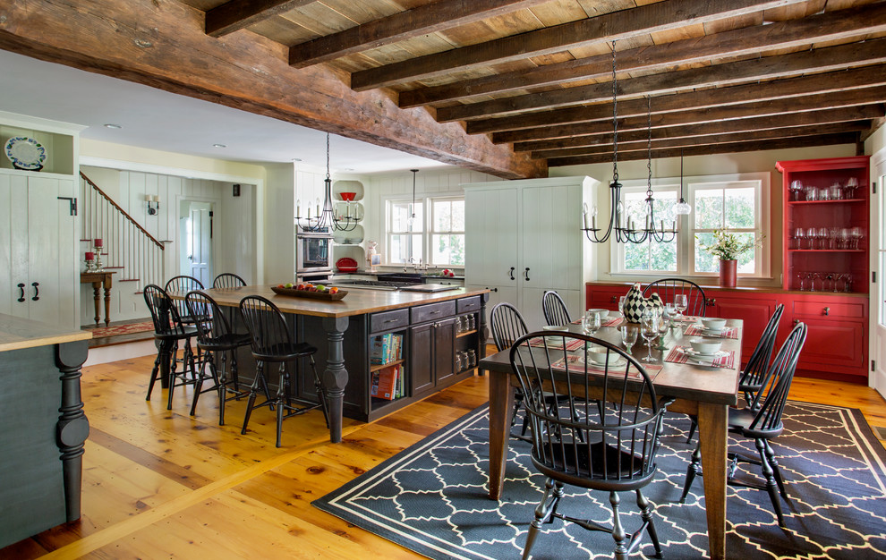 Mid-sized cottage u-shaped light wood floor eat-in kitchen photo in Boston with a farmhouse sink, white cabinets, white appliances, an island, beaded inset cabinets, white backsplash, stone slab backsplash and wood countertops