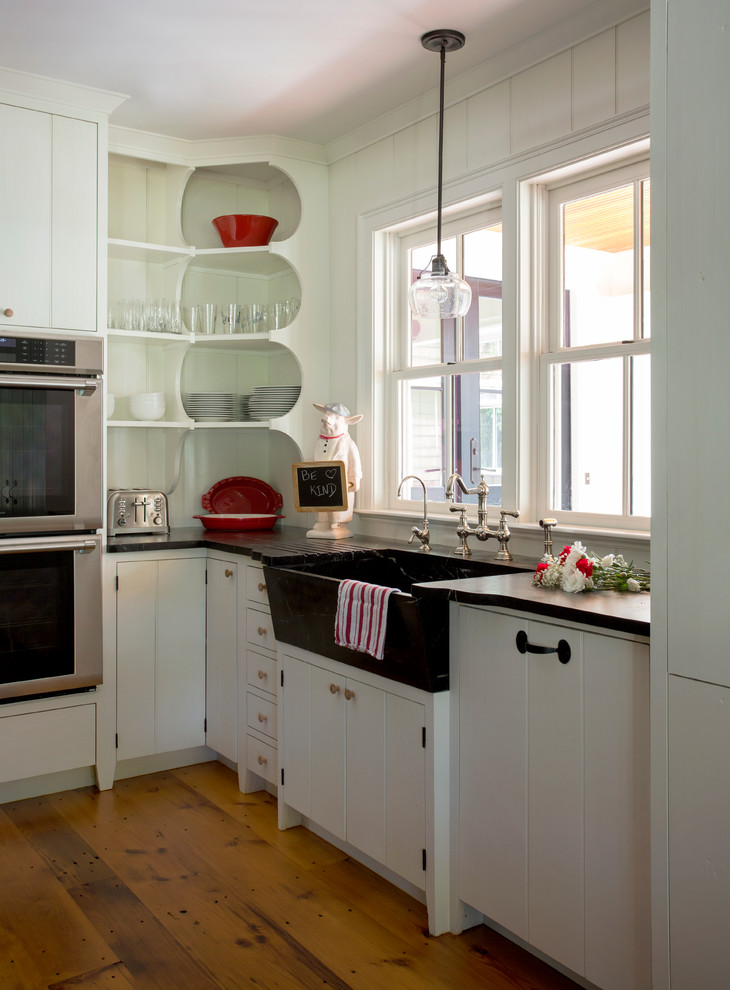 Example of a mid-sized farmhouse light wood floor kitchen design in Boston with a farmhouse sink, white cabinets, soapstone countertops, stainless steel appliances, an island and white backsplash