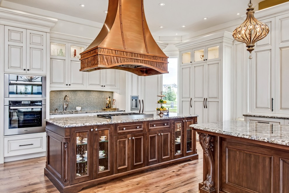 Large elegant l-shaped medium tone wood floor and brown floor eat-in kitchen photo in Calgary with an undermount sink, raised-panel cabinets, white cabinets, granite countertops, gray backsplash, mosaic tile backsplash, stainless steel appliances and two islands