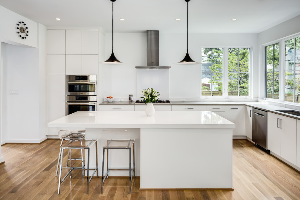 Example of a mid-sized minimalist l-shaped light wood floor and beige floor open concept kitchen design in DC Metro with an undermount sink, flat-panel cabinets, white cabinets, quartzite countertops, stainless steel appliances and an island