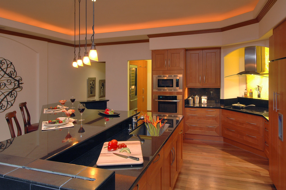 Kitchen - traditional kitchen idea in Hawaii with a single-bowl sink, shaker cabinets, medium tone wood cabinets, black backsplash and paneled appliances