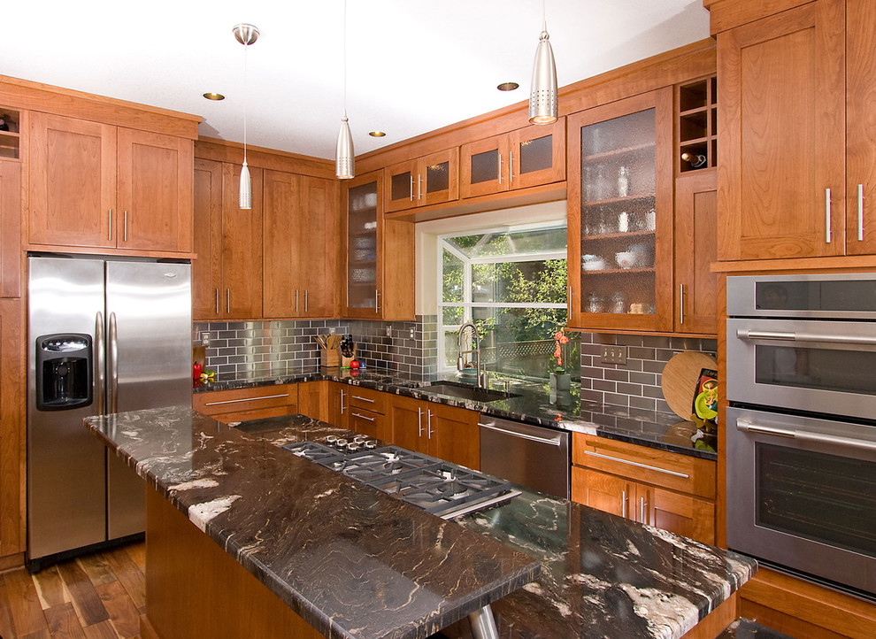 Example of a transitional kitchen design in Portland with stainless steel appliances, a single-bowl sink, shaker cabinets, medium tone wood cabinets, granite countertops, metallic backsplash and metal backsplash