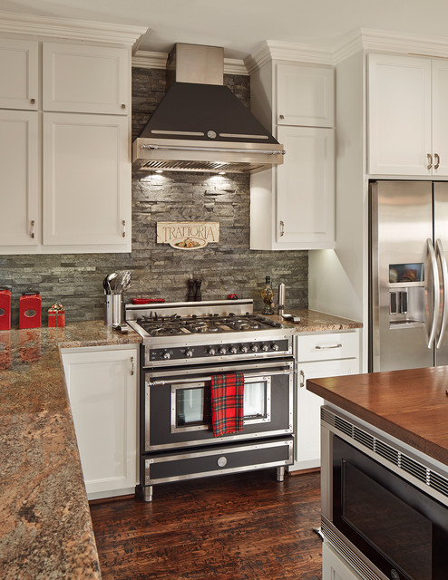 Example of a mid-sized classic u-shaped dark wood floor and brown floor kitchen design in Dallas with recessed-panel cabinets, white cabinets, gray backsplash, black appliances, slate backsplash, granite countertops and an island