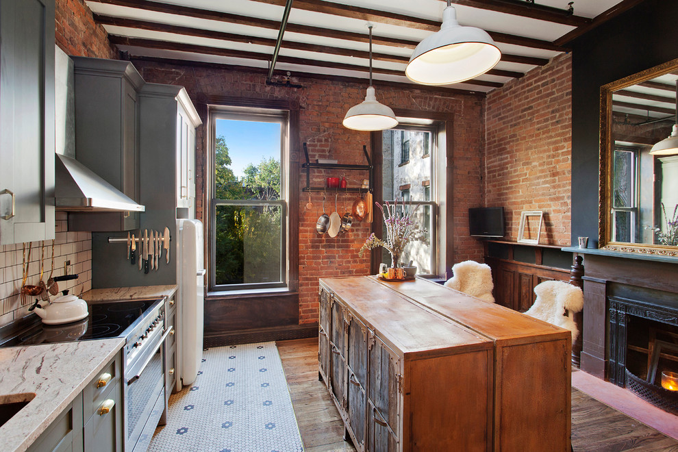 Example of a mid-sized eclectic single-wall ceramic floor kitchen design in New York with an undermount sink, shaker cabinets, gray cabinets, granite countertops, white backsplash, subway tile backsplash, stainless steel appliances and an island