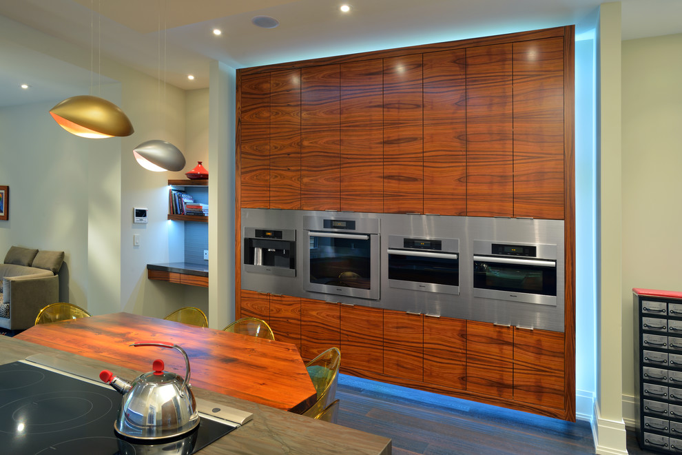 Enclosed kitchen - mid-sized contemporary galley dark wood floor enclosed kitchen idea in Toronto with stainless steel appliances, flat-panel cabinets, medium tone wood cabinets, onyx countertops, blue backsplash, glass tile backsplash and an island
