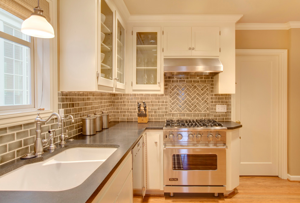 Kitchen - traditional kitchen idea in Seattle with a double-bowl sink, glass-front cabinets, beige backsplash, subway tile backsplash, stainless steel appliances and white cabinets