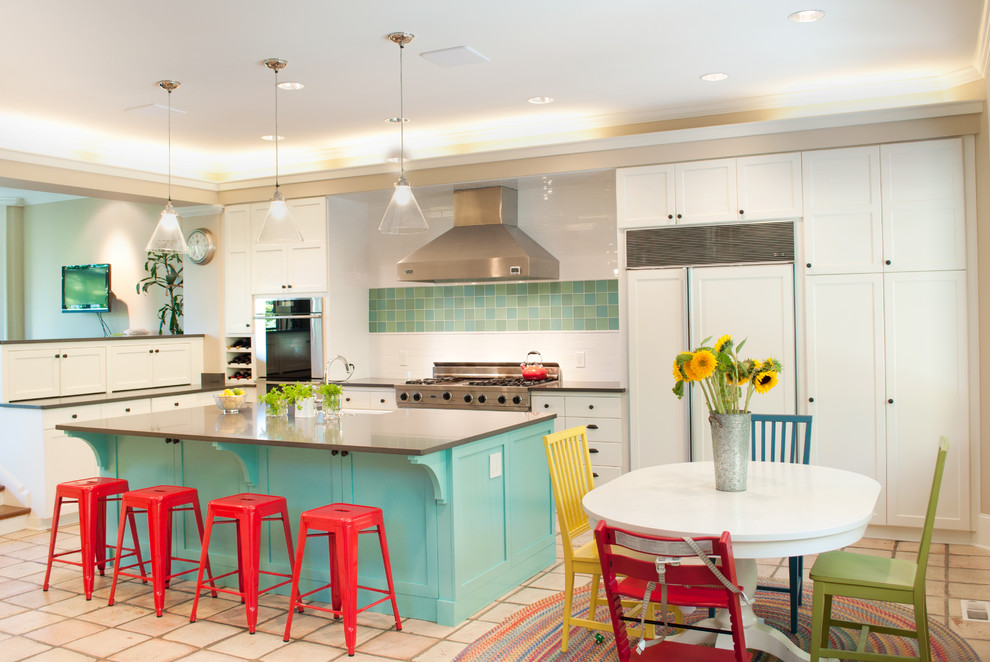 Eat-in kitchen - large modern u-shaped terra-cotta floor and beige floor eat-in kitchen idea in Seattle with white cabinets, stainless steel appliances, a farmhouse sink, raised-panel cabinets, solid surface countertops, white backsplash, subway tile backsplash and an island