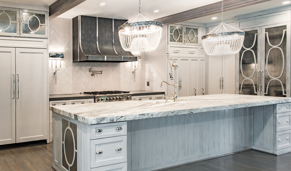 Example of a huge eclectic u-shaped light wood floor eat-in kitchen design in Houston with a farmhouse sink, glass-front cabinets, white cabinets, white backsplash, porcelain backsplash, stainless steel appliances, an island and marble countertops
