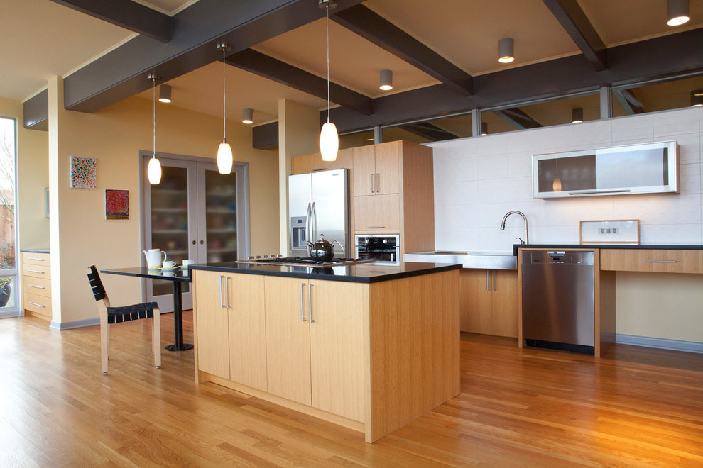 Inspiration for a large 1950s galley medium tone wood floor eat-in kitchen remodel in Seattle with flat-panel cabinets, light wood cabinets, granite countertops, stainless steel appliances, white backsplash and an island