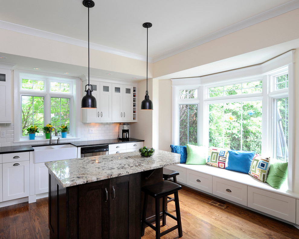 Inspiration for a timeless l-shaped kitchen remodel in Ottawa with subway tile backsplash, a farmhouse sink, granite countertops, shaker cabinets, white cabinets, white backsplash and gray countertops