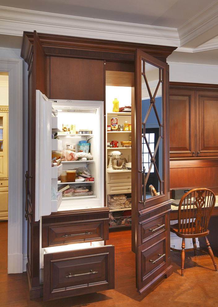 Example of a classic kitchen design in Dallas with raised-panel cabinets and dark wood cabinets