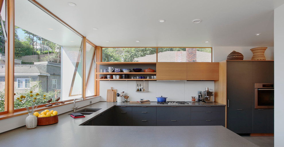 Inspiration for a mid-sized modern u-shaped concrete floor and gray floor enclosed kitchen remodel in Seattle with flat-panel cabinets, a double-bowl sink, medium tone wood cabinets, black appliances, quartz countertops, white backsplash and a peninsula