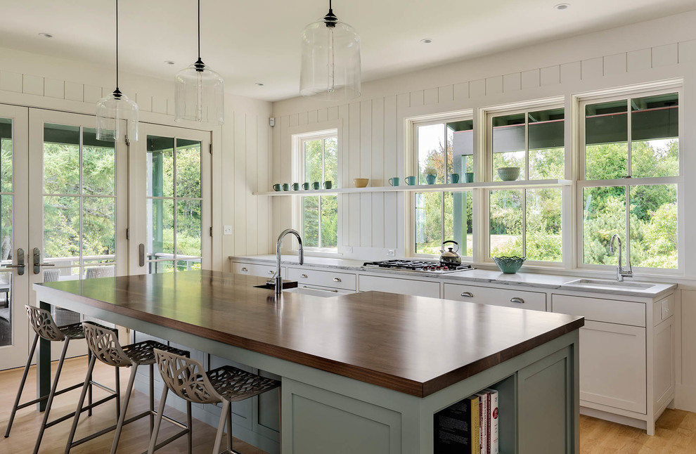 Mid-sized beach style galley light wood floor eat-in kitchen photo in Portland Maine with a single-bowl sink, shaker cabinets, white cabinets, an island, wood countertops, white backsplash and stainless steel appliances