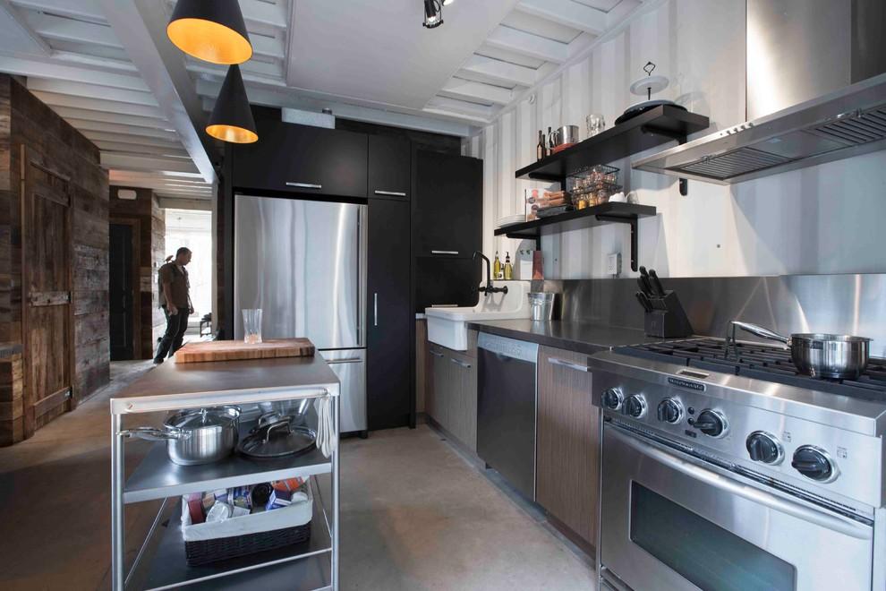 Foto de cocina urbana con fregadero sobremueble, puertas de armario marrones, encimera de acero inoxidable, salpicadero blanco, salpicadero de metal y electrodomésticos de acero inoxidable