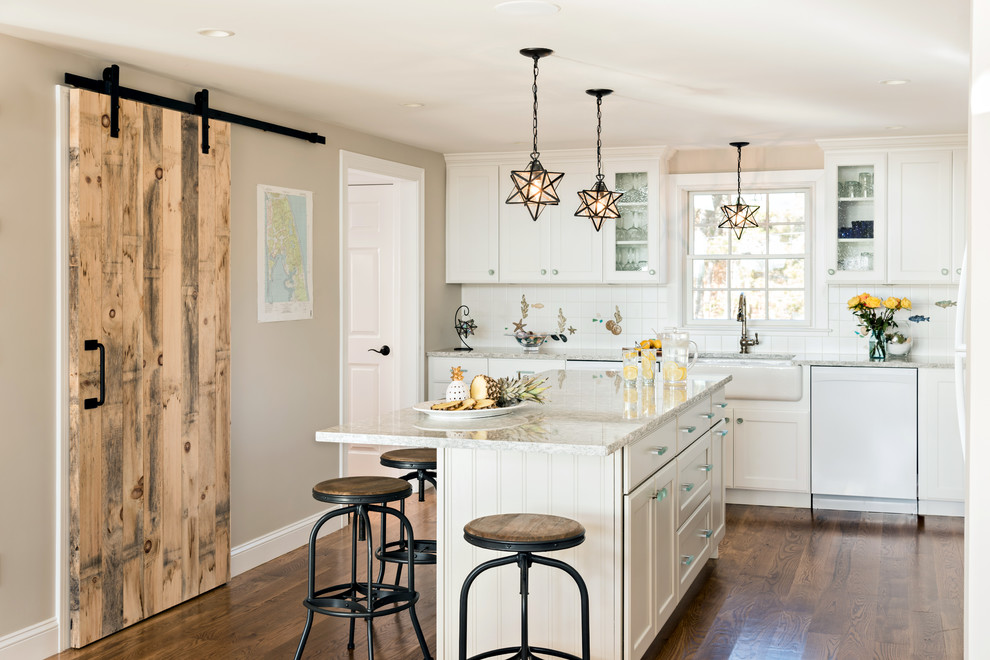 Mid-sized beach style l-shaped dark wood floor and brown floor enclosed kitchen photo in Boston with a farmhouse sink, white cabinets, white backsplash, white appliances, an island, glass-front cabinets, beige countertops, granite countertops and ceramic backsplash