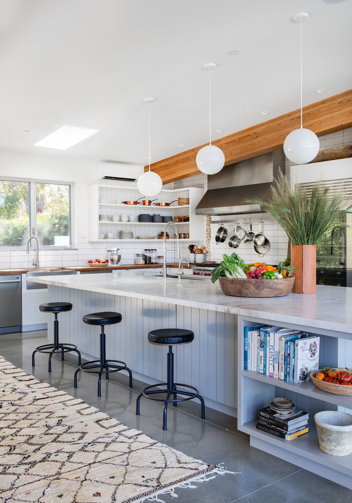 Contemporary l-shaped eat-in kitchen in Los Angeles with a farmhouse sink, white splashback, subway tile splashback, stainless steel appliances, with island, grey floor, white benchtop and concrete floors.