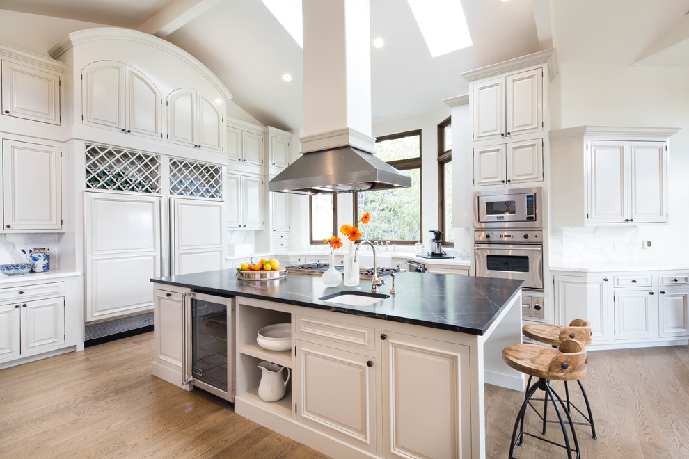 Example of a large classic u-shaped light wood floor eat-in kitchen design in San Francisco with raised-panel cabinets, white cabinets, white backsplash, stainless steel appliances, an island, a farmhouse sink, soapstone countertops and stone slab backsplash
