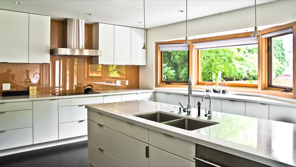 Example of a minimalist kitchen design in Vancouver with an undermount sink, flat-panel cabinets, white cabinets, orange backsplash and glass sheet backsplash