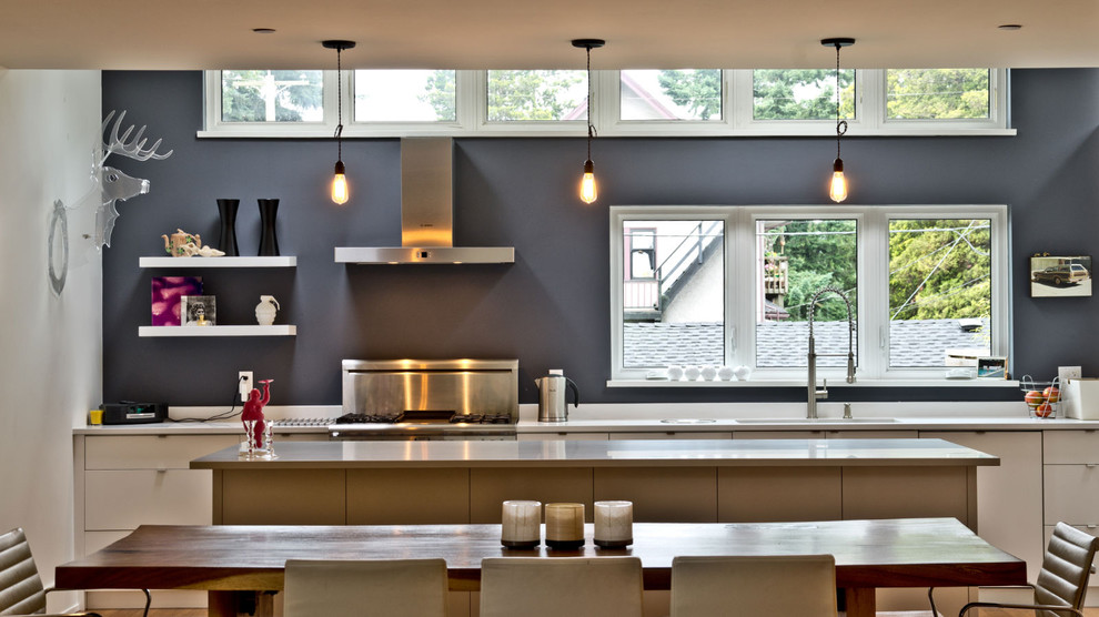 Eat-in kitchen - modern single-wall eat-in kitchen idea in Vancouver with stainless steel appliances, flat-panel cabinets and white cabinets